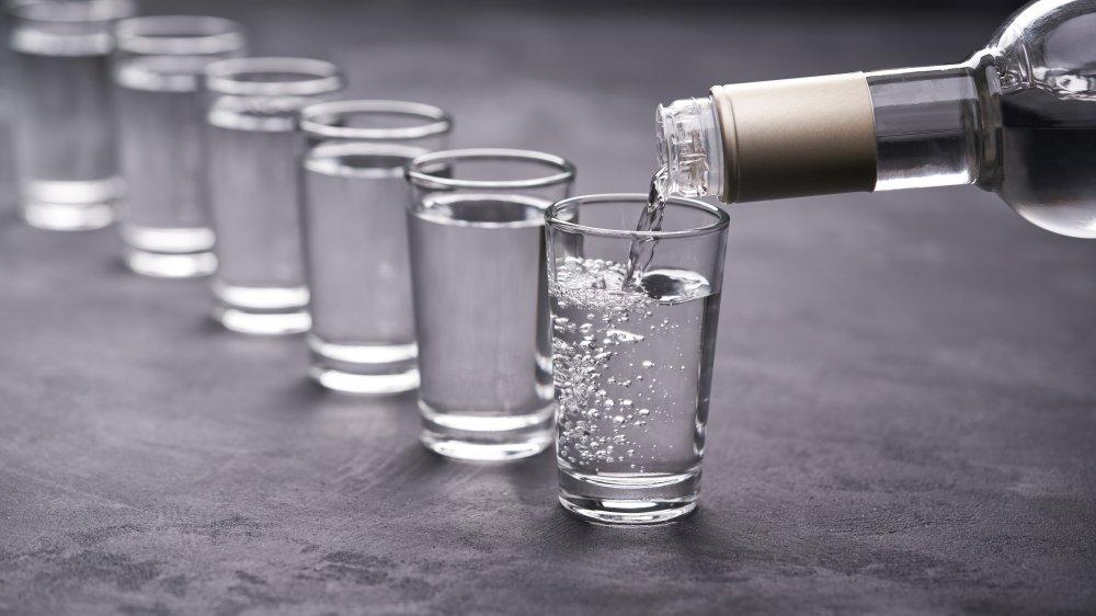 A bottle of vodka pouring shots into glasses