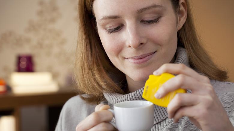 Woman adding artificial sweeteners