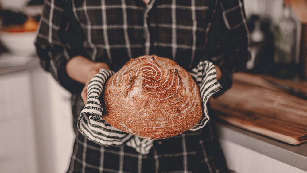 A woman holding a loaf of sourdough bread