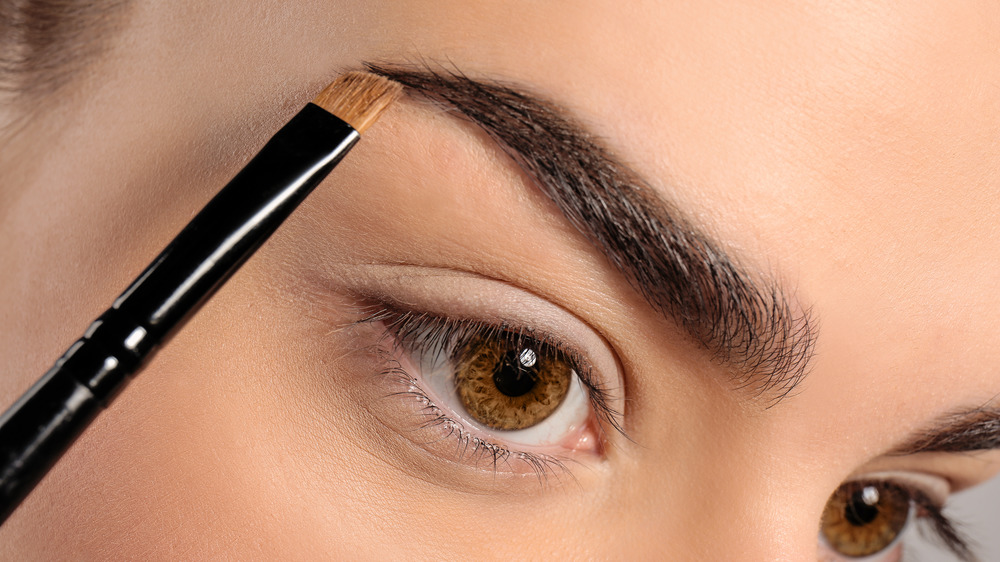 Woman putting on eyebrow makeup
