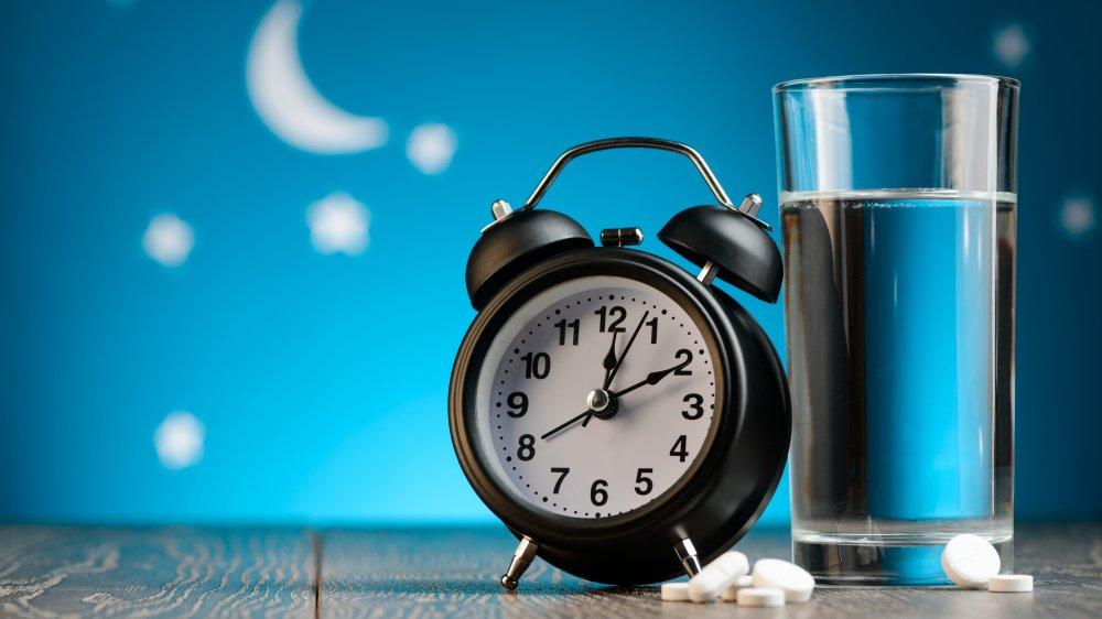 alarm clock, sleeping pills, water