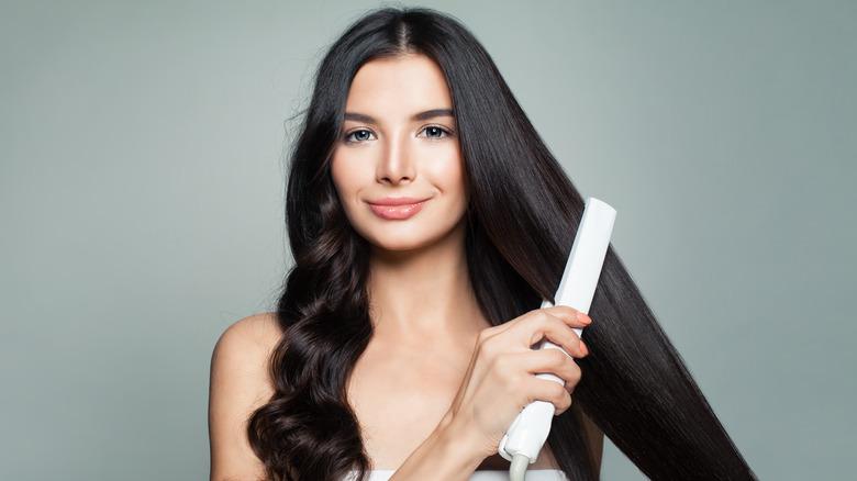 Brunette woman straightening hair