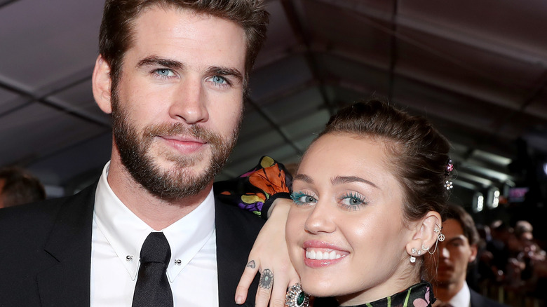 Miley Cyrus and Liam Hemsworth pose on the red carpet