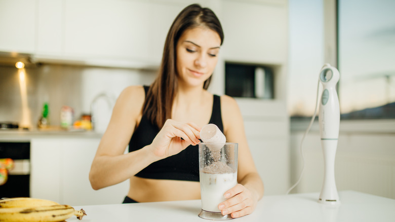 Fit woman preparing a whey protein shake
