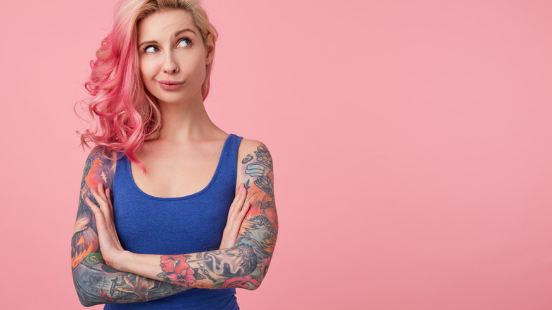 Woman with pink and blonde hair and blue tank top with tattooed arms folded is looking up with a questioning look