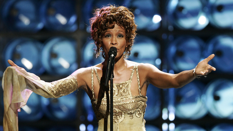 Whitney Houston singing in gold dress
