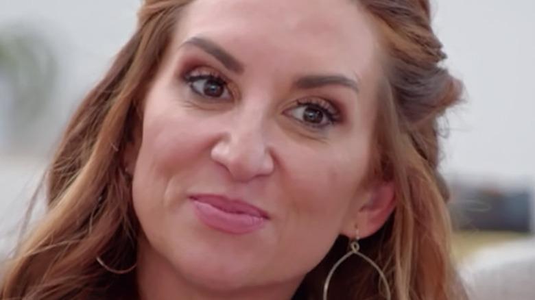Sarah Miller in hoop earrings grinning