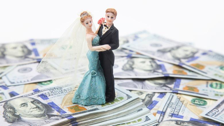 Wedding cake topper on top of hundred dollar bills.