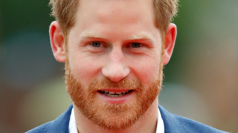 Prince Harry poses for the camera at an event.