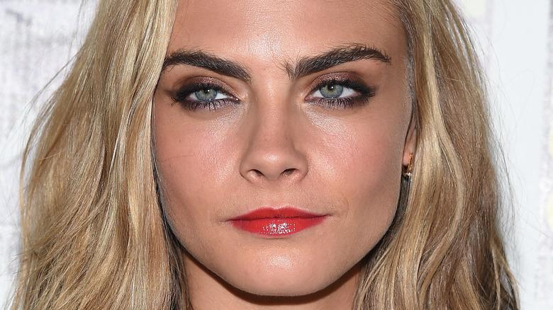Cara Delevingne red lipstick dark eyebrows blond