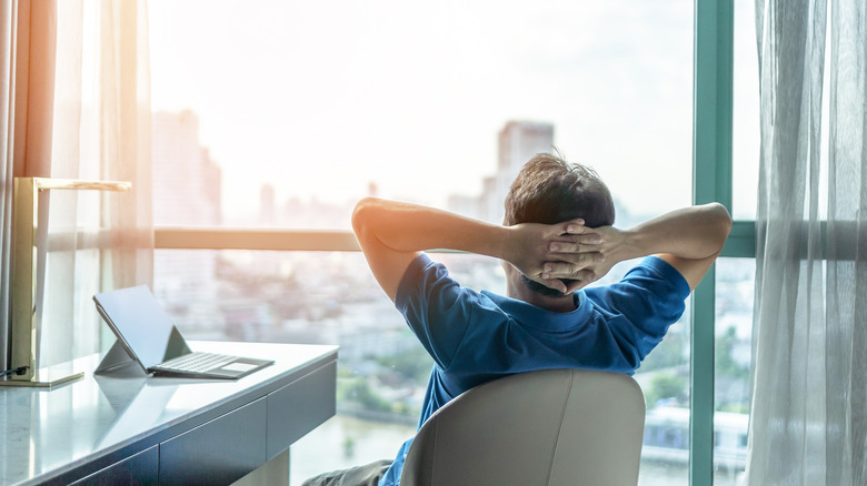 Relaxed man looking out city window