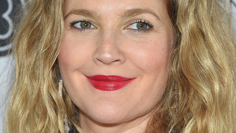 Drew Barrymore posing at event with slight smile and red lipstick