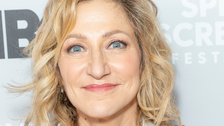 Edie Falco grinning with hair down