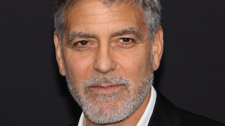 George Clooney smiles with a gray beard.