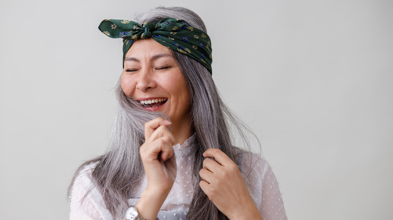 Woman with gray hair and green headband