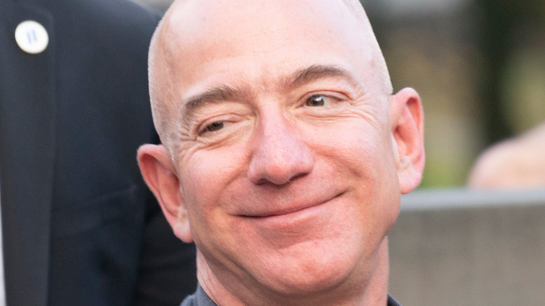 Jeff Bezos smiling in a gray suit