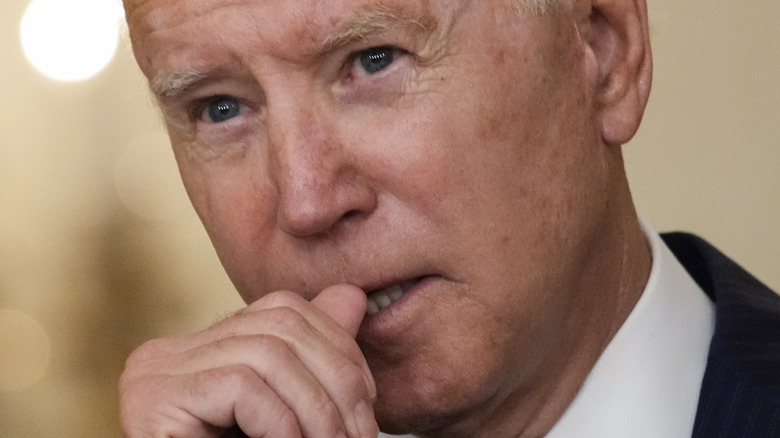 close up of Joe Biden with his hand to his mouth
