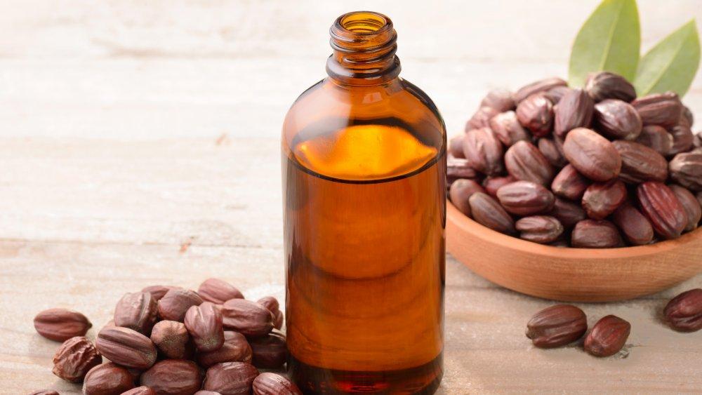 bottle of jojoba oil and seeds on wood board