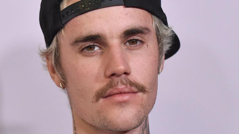 Justin Bieber wearing cap, white sweatshirt, 2020
