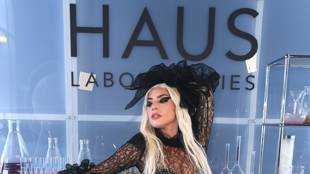 Lady Gaga poses in front of Haus Laboratories sign
