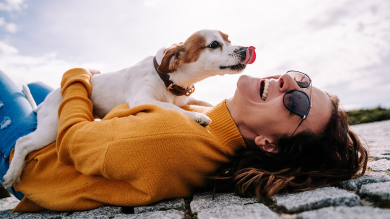 Woman laughing while holding a dog