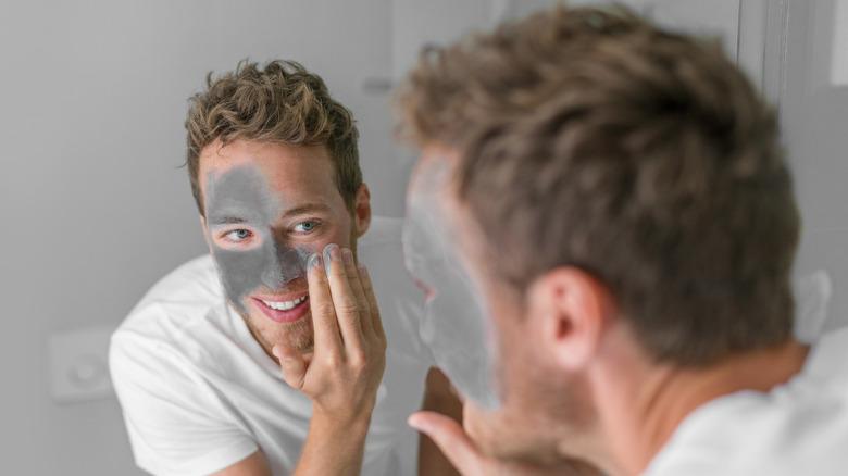 Man putting on a mud mask