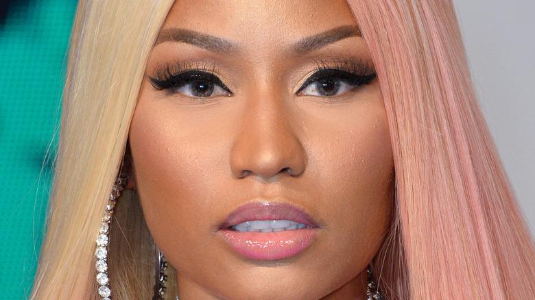 Nicki Minaj wears diamond earrings with straight blonde hair.