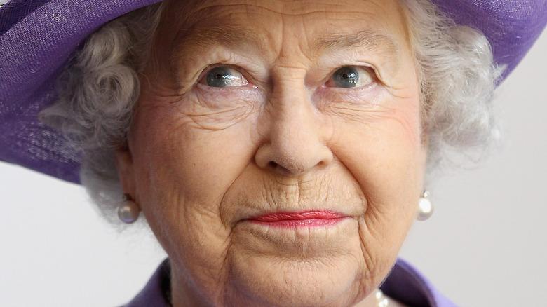 Queen Elizabeth smiling wearing all purple