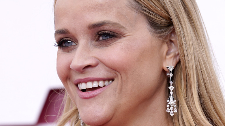 Reese Witherspoon smiling with hair down and long diamond earrings