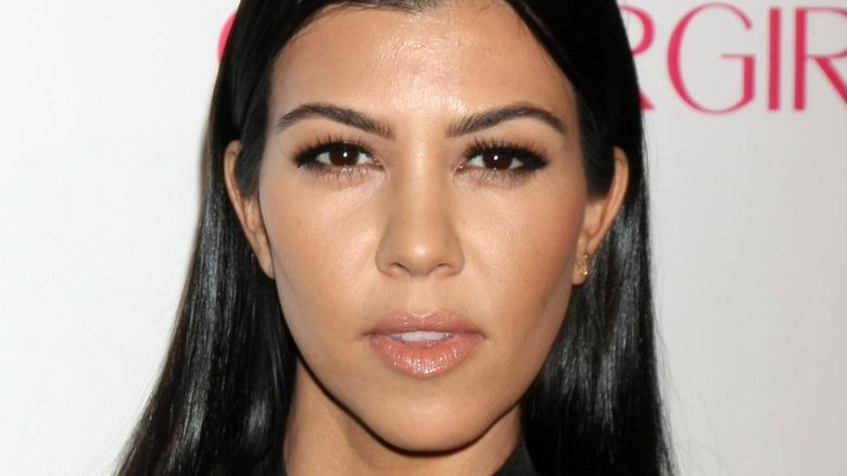 Kourtney Kardashian wears a black dress at an event.