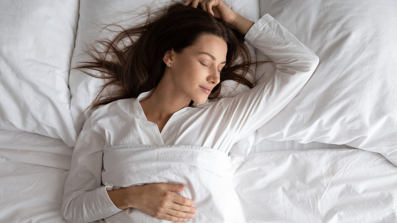 Woman sleeping on her back with her arm above her head
