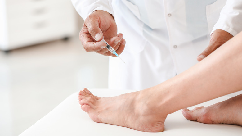 Doctor with syringe over foot