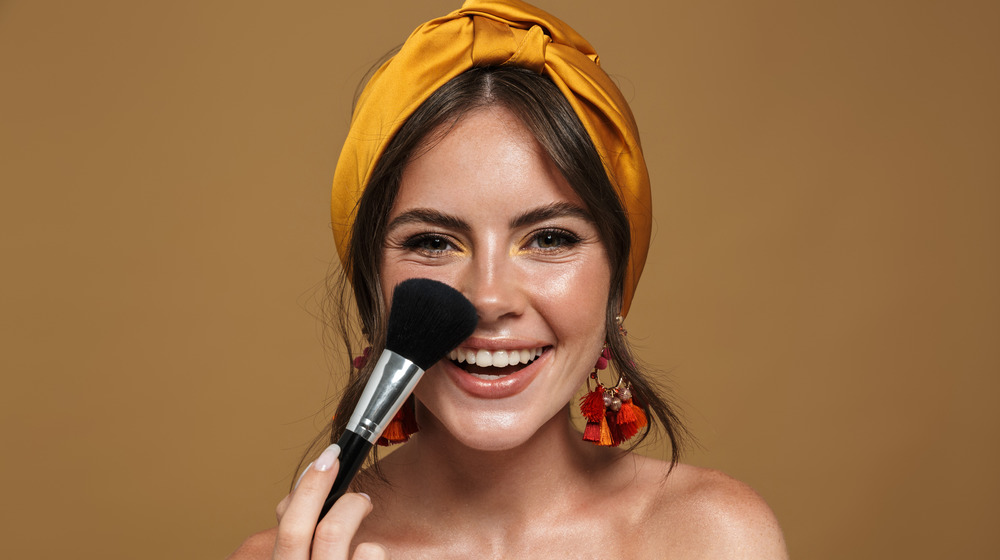 A smiling woman applying makeup