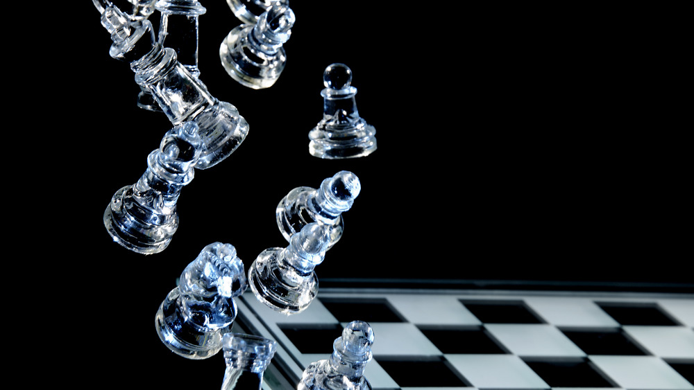 Glass chess pieces falling on a board