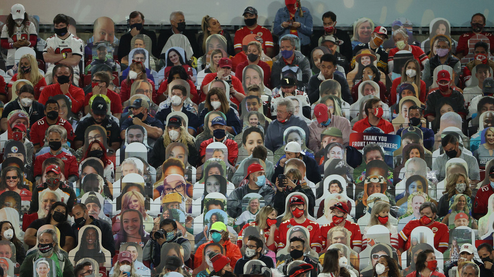 Fans mingle with cardboard cutouts at the stadium