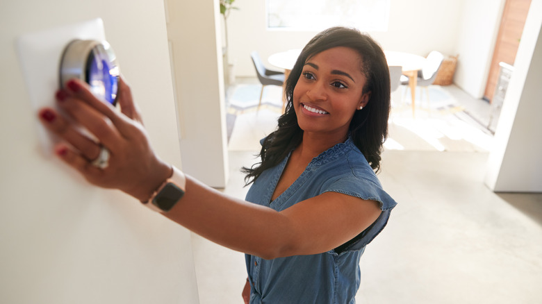 Woman adjusting her thermostat