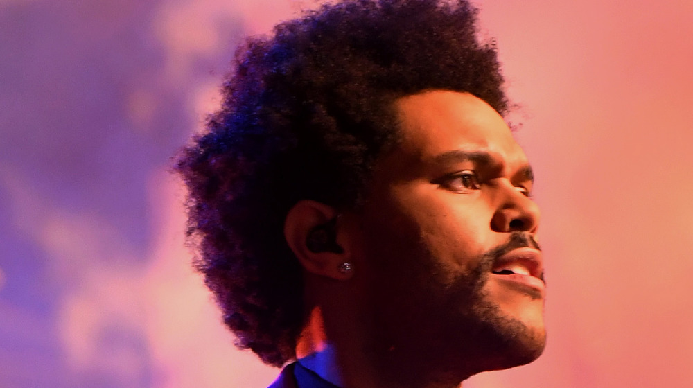 The Weeknd at Super Bowl smiling with earpiece