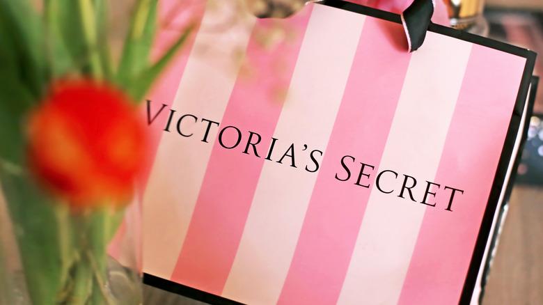 Victoria's Secret bag behind a flower vase