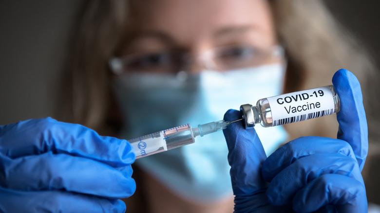 Women holding COVID-19 vaccine