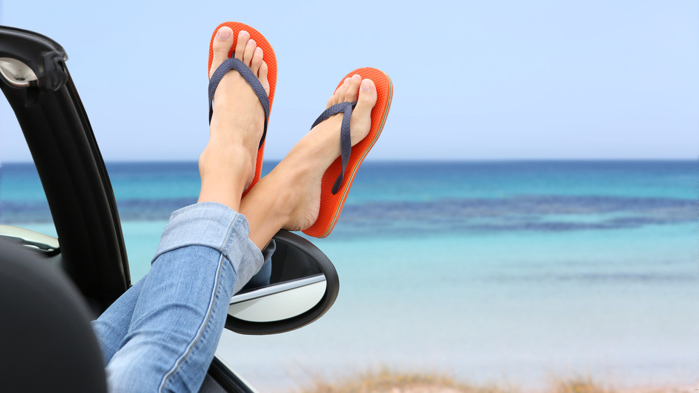 Person with flip-flops sticking feet out car window