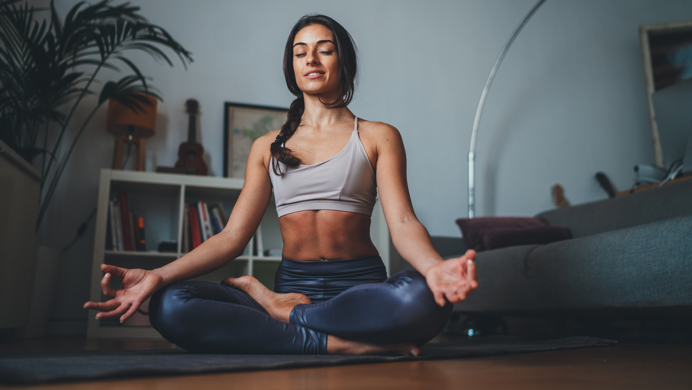 Woman practicing yoga barefoot at home