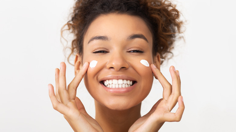 smiling woman applying white cream to her face