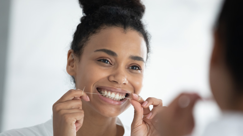 A smiling woman flossing her teeth