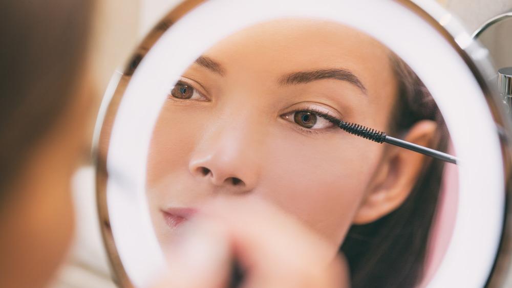 A woman applying mascara in a mirror