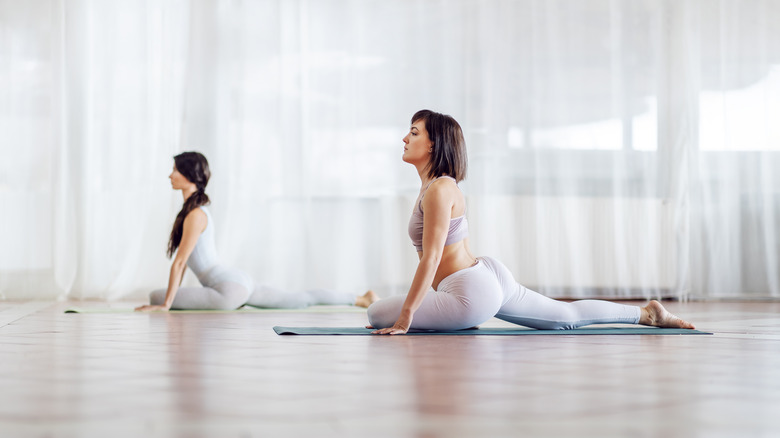 Two women doing pigeon pose