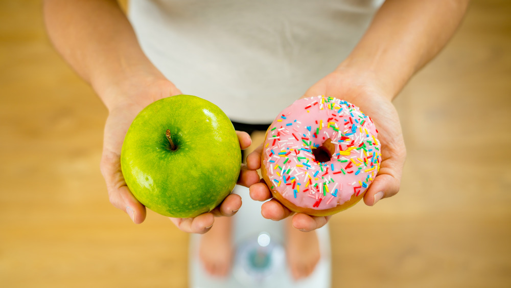 Woman holding apple and donut