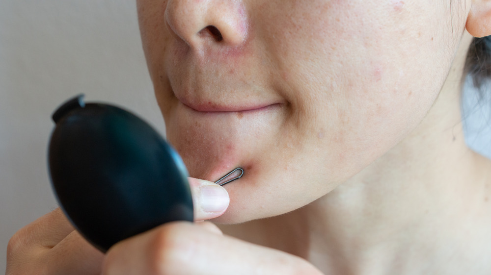 Woman extracting her own pimples