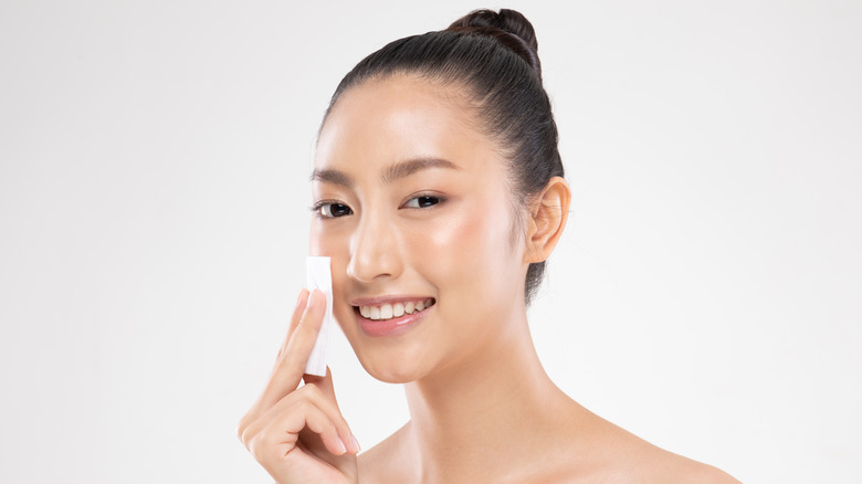 Woman wiping face with toner