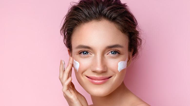 A woman applying moisturizer