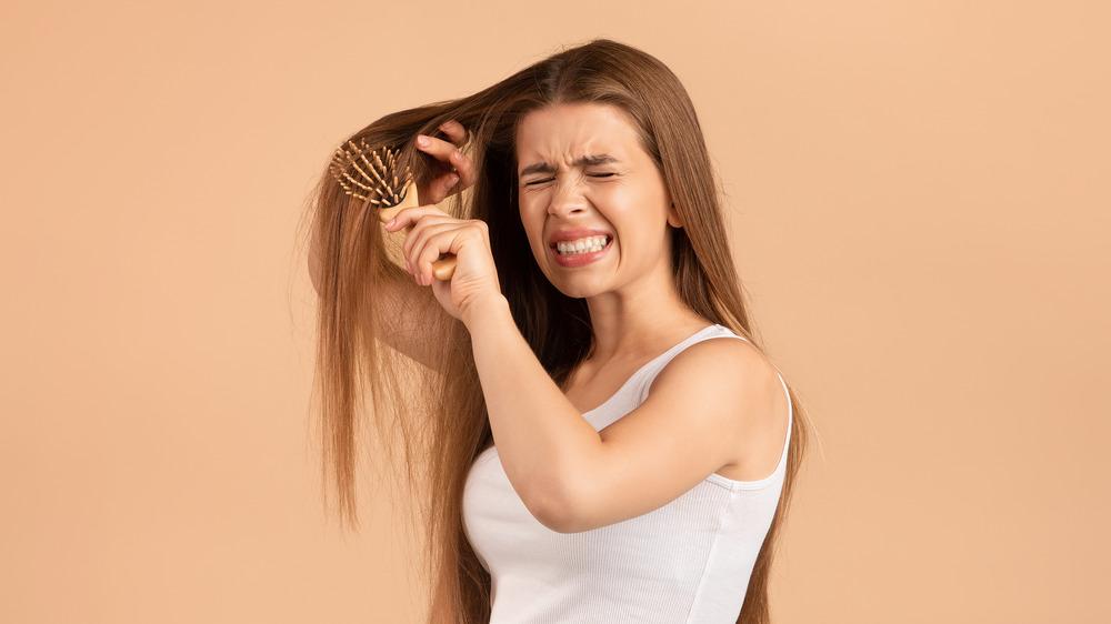 Girl brushing knotty hair